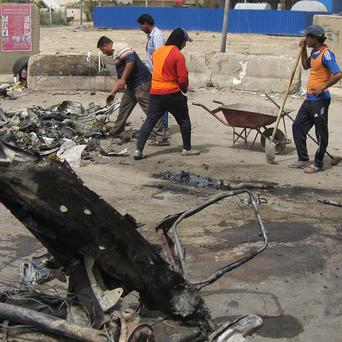 Workers clean up after a car bomb attack in Baghdad (AP)