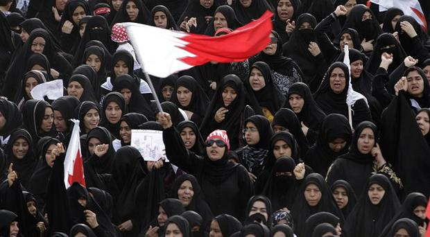 Bahraini anti-government protesters wave national flags during a march (AP)