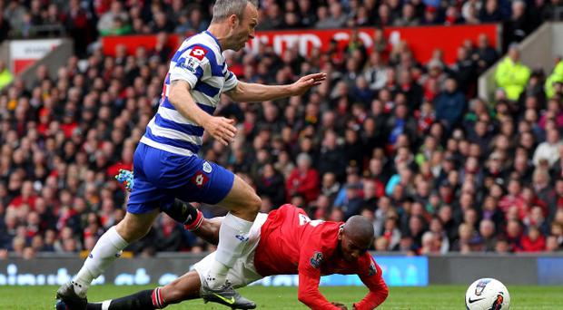 MANCHESTER, ENGLAND - APRIL 08: Shaun Derry of Queens Park Rangers brings down Ashley Young of Manchester United to concede a penalty during the Barclays Premier League match between Manchester United and Queens Park Rangers at Old Trafford on April 8, 2012 in Manchester, England. (Photo by Alex Livesey/Getty Images)