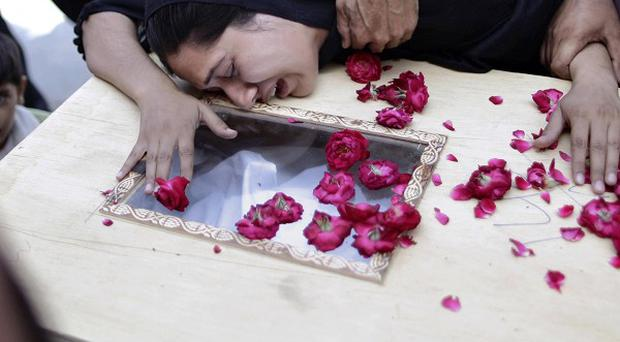 The sister of a Pakistani man, who lost his life when Bhoja Air plane crashed, cries over his coffin outside a hospital in Islamabad (AP)