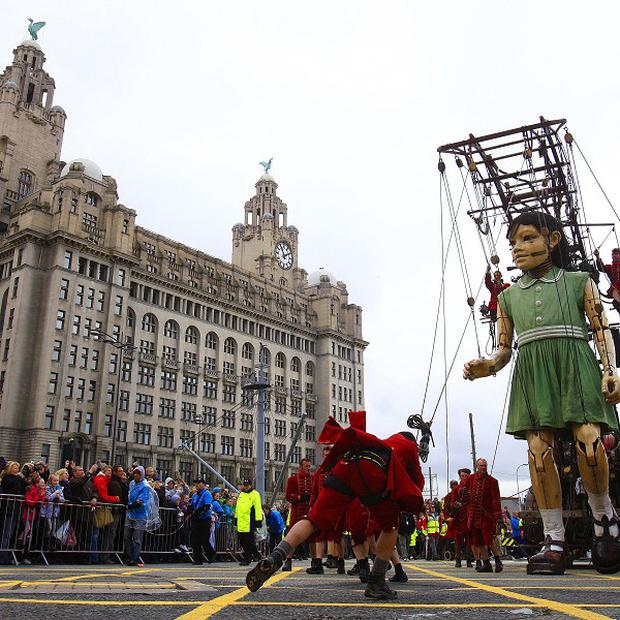 The Little Giant Girl is hoisted into the air outside Liver building, Liverpool, for street theatre performance Sea Odyssey