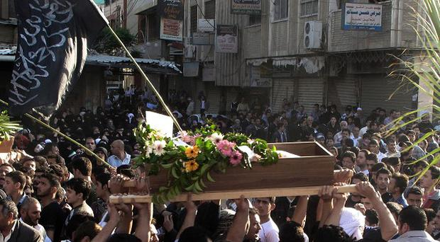 Syrian mourners carry the bodies of an infant and a Free Syrian Army fighter during their funeral in Damascus (AP)