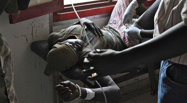 A South Sudanese soldier has a bullet removed from his leg at Rubkona Military Hospital (AP)