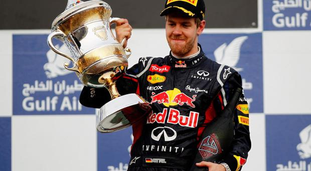 SAKHIR, BAHRAIN - APRIL 22: Sebastian Vettel of Germany and Red Bull Racing celebrates on the podium after winning the Bahrain Formula One Grand Prix at the Bahrain International Circuit on April 22, 2012 in Sakhir, Bahrain. (Photo by Paul Gilham/Getty Images)