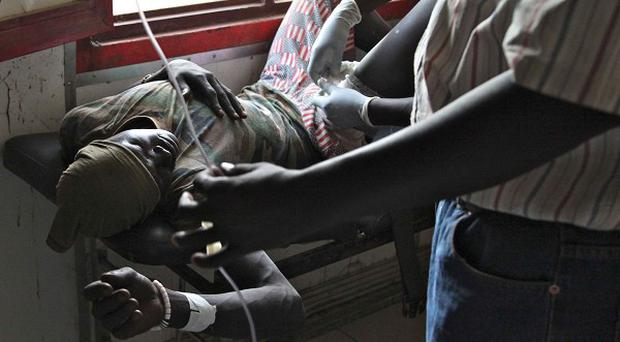 A soldier has a bullet removed from his leg as bomb attacks drop near Bentiu, killing a boy and injuring two others (AP)