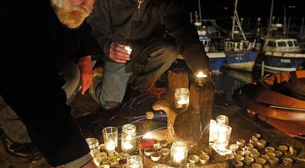 Residents lit candles at a memorial on the pier at Union Hall, Cork, after the Tit Bonhomme trawler sunk
