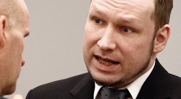 Anders Breivik (right) talks with defence lawyer Geir Lippestad (AP)