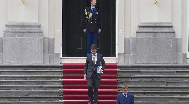 Dutch prime minister Mark Rutte leaving the royal palace after handing in his resignation to Queen Beatrix (AP)