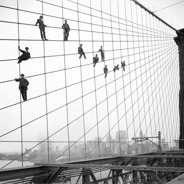 Painters are suspended from wires on the Brooklyn Bridge in New York, one of the city's archive photos put online (AP)