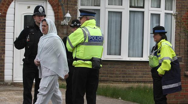 Officers stand guard outside an address on Bishopscote Road in Luton as police examine the inside of the home