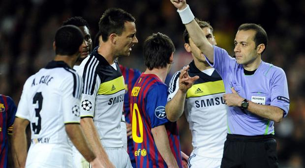 Referee Cuneyt Cakir, right, shows a red card to Chelsea's John Terry during a semifinal second leg Champions League soccer match against FC Barcelona at the Camp Nou stadium in Barcelona, Spain, Tuesday, April 24, 2012. (AP Photo/Manu Fernandez)