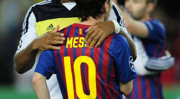 Chelsea's Didier Drogba, left, embraces Lionel Messi, from Argentina, at the end of the semifinal second leg Champions League soccer match at the Camp Nou stadium in Barcelona, Spain, Tuesday, April 24, 2012. The match ended in a 2-2 draw. (AP Photo/Manu Fernandez)
