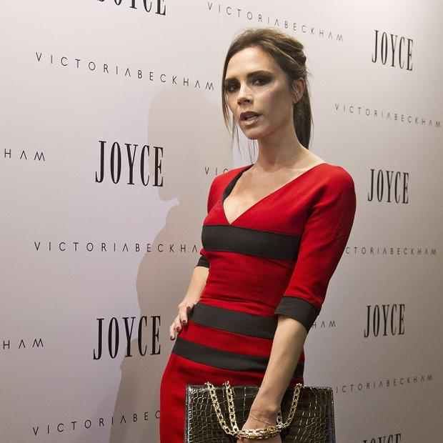 Victoria Beckham poses in a red dress during her trip to China