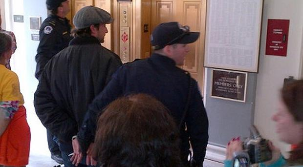 Handcuffed actor Noah Wyle, centre, on Capitol Hill in Washington