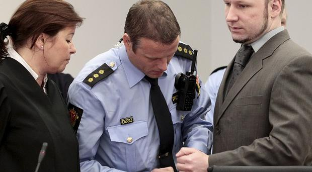 Anders Breivik has his handcuffs removed at the start of court proceedings (AP)