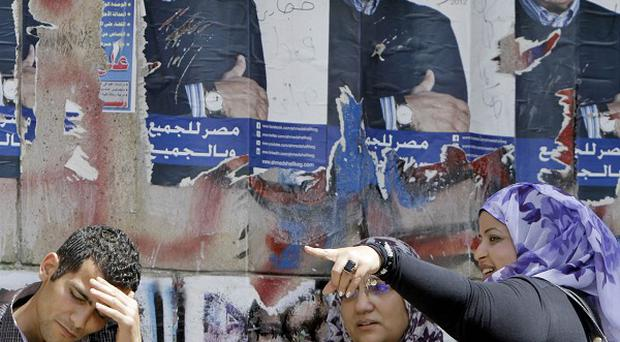 Egyptians chat under defaced posters of Presidential candidate Ahmed Shafiq (AP)