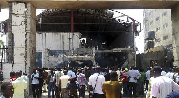 People gather in front of the bombed office of the newspaper ThisDay(AP)