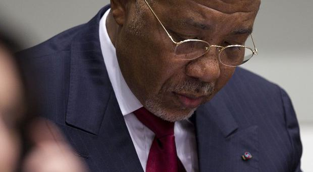 Ex-Liberian President Charles Taylor takes notes as he waits for the verdict in his war crimes trial(AP)