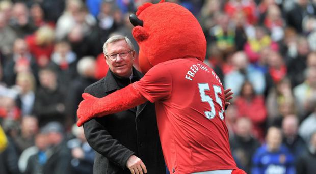 Sir Alex Ferguson is hugged by Manchester United mascot Fred the Red