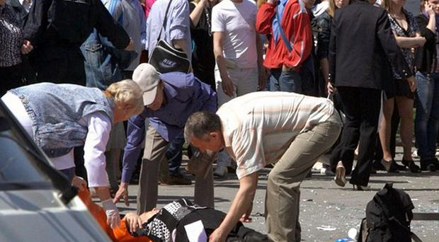 Bystanders help a person injured in one of the blasts in Dnipropetrovsk (AP)