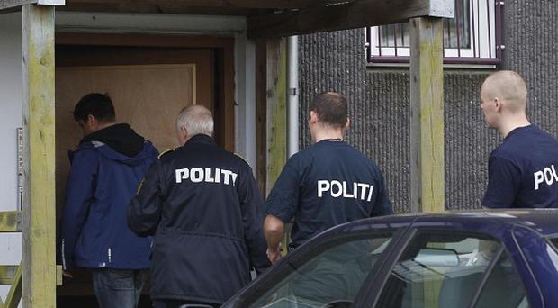 Danish police enter an apartment complex in Herlev, on the outskirts of Copenhagen, for a search (AP)