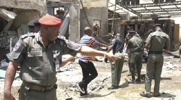 A police officer points at the site of a bomb explosion in Abuja, Nigeria(AP/Gbemiga Olamikan)