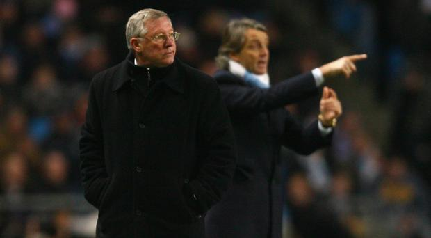 MANCHESTER, ENGLAND - JANUARY 19: Manchester United Manager Sir Alex Ferguson looks on as Manchester City Manager Roberto Mancini gestures during the Carling Cup Semi Final match between Manchester City and Manchester United at the City of Manchester Stadium on January 19, 2010 in Manchester, England. (Photo by Alex Livesey/Getty Images)