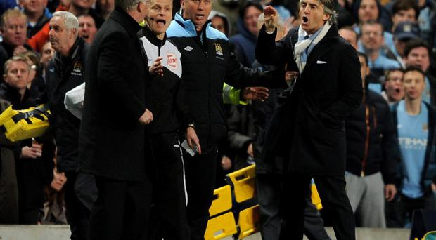 MANCHESTER, ENGLAND - APRIL 30: Manchester United Manager Sir Alex Ferguson clashes with Manchester City Manager Roberto Mancini (R) during the Barclays Premier League match between Manchester City and Manchester United at the Etihad Stadium on April 30, 2012 in Manchester, England. (Photo by Michael Regan/Getty Images)