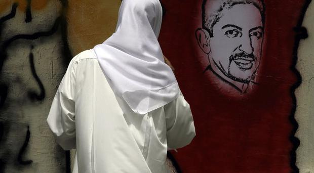 A Bahraini man looks at an image of jailed hunger striker Abdulhadi al-Khawaja painted on a wall (AP)