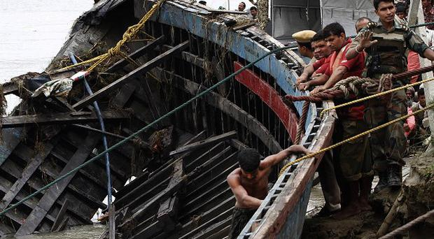 Rescuers salvage the wreckage of a ferry that capsized in the Brahmaputra River at Buraburi village, India (AP)