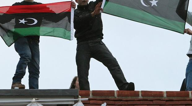 Protesters demonstrate on the roof of a house thought to belong to Saif al-Islam Gaddafi in north London