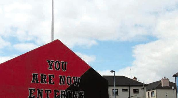 Makeover: Free Derry Corner has been painted red and black to mark anniversary of death of civil rights leader John McGuffin