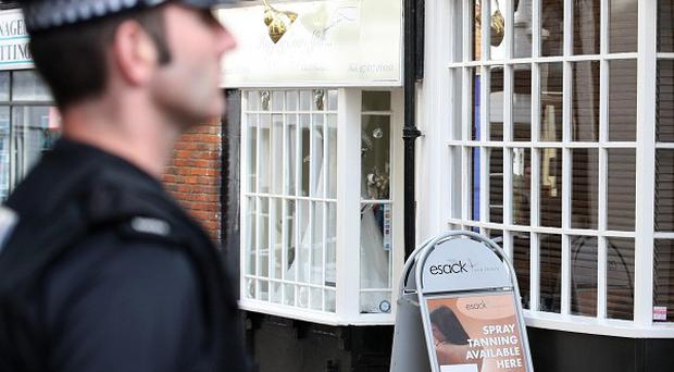 A police officer stands outside Esack Hair and Beauty in Ashford, Kent, where Natalie Esack was discovered with fatal stab wounds