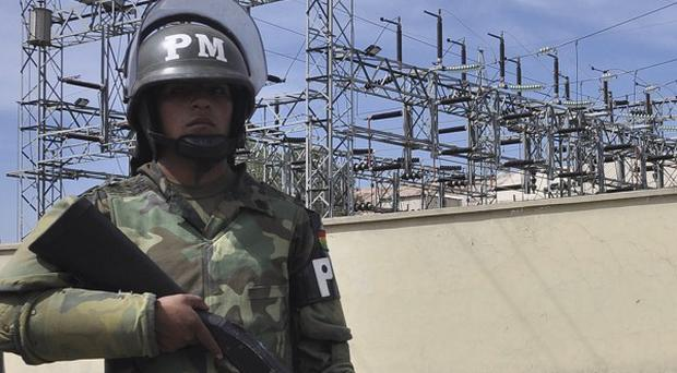 Military police stand guard outside Transportadora de Electricidad after the Bolivian president Evo Morales nationalised the electricity sector (AP)