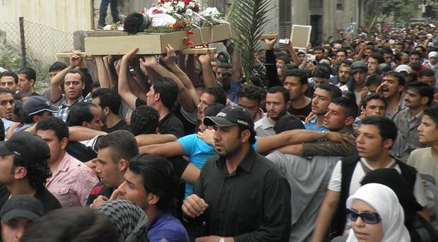 Anti-Syrian regime mourners carry the body of a killed activist during his funeral procession in Damascus (AP)