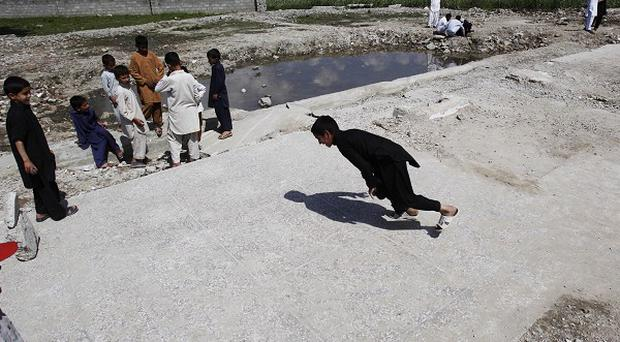 Pakistani boys play at the demolished compound of Osama bin Laden in Abbottabad, Pakistan (AP)