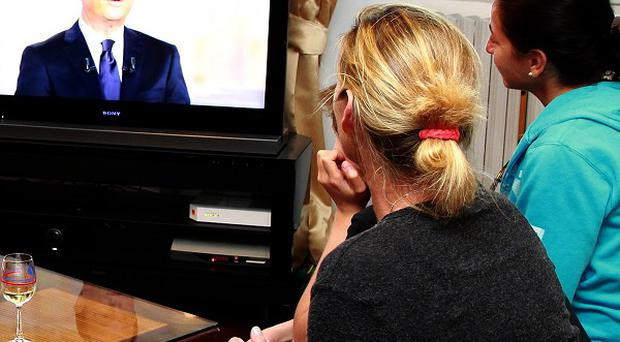 A family listens to Socialist Party candidate for the French presidential election Francois Hollande speaking during a televised debate (AP)