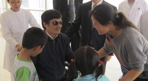Chen Guangcheng was reunited with his wife Yuan Weijing and children at a hospital in Beijing (AP)