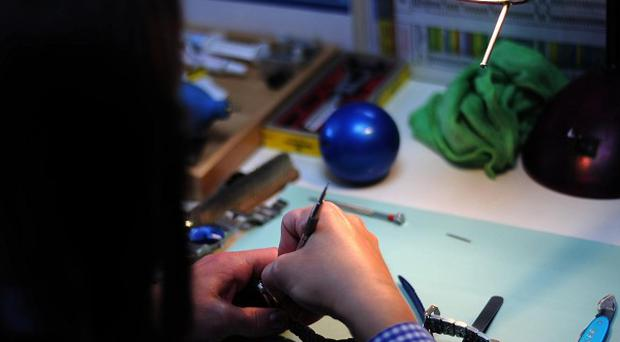 A prisoner repairs a watch at a Timpson training academy for prisoners at HMP Blantyre House, Kent