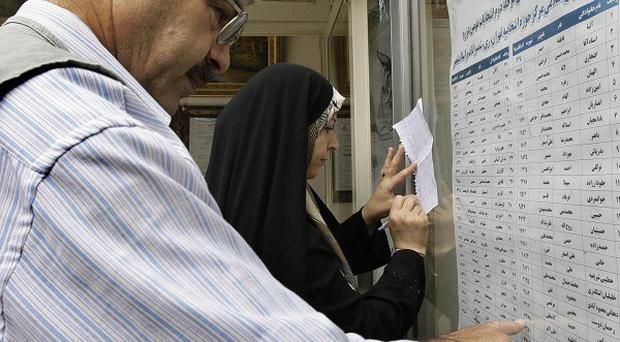 An Iranian couple check the list of candidates at a polling station in Tehran (AP)
