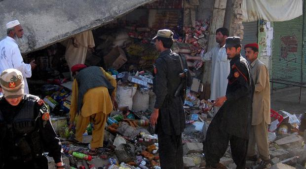 Security personnel visit the site of a suicide bombing in the Pakistani tribal region of Khar in Bajur (AP)