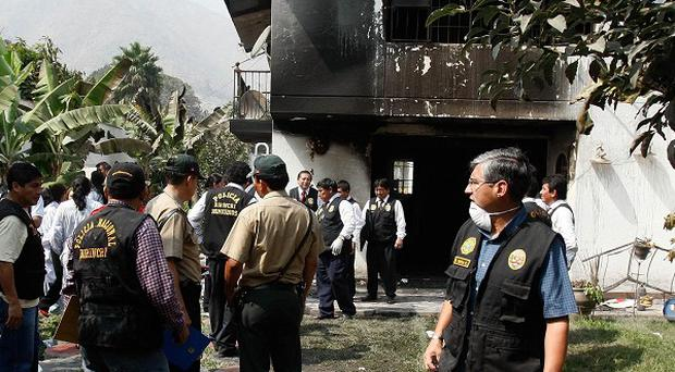 Police officers stand outside the site of a pre-dawn blaze, at the Sacred Heart of Jesus clinic in Chosica, Peru (AP)