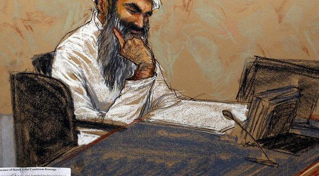 Khalid Sheikh Mohammed reads a document during his military hearing at Guantanamo Bay (AP/Sketch byJanet Hamlin)