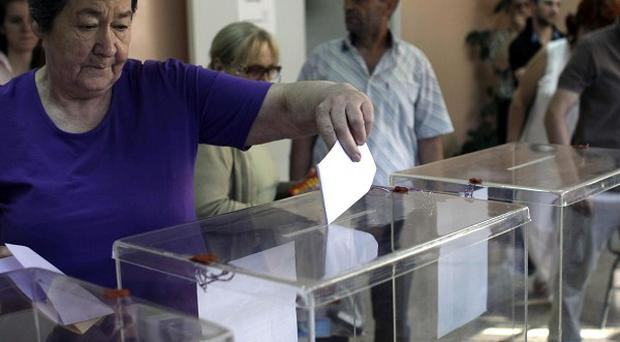 A woman casts her ballot at a polling station in Belgrade, Serbia (AP)