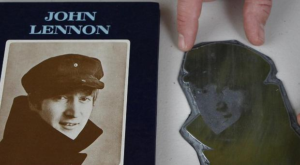 Auctioneer Paul Fairweather positions an image on a printers plate of John Lennon, alongside a book by the Beatles musician 'In His Own Write' at Omega Auctions in Stockport