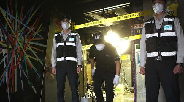 South Korean police officers stand guard at the entrance to a karaoke bar where a fire broke out in Busan, South Korea (AP)