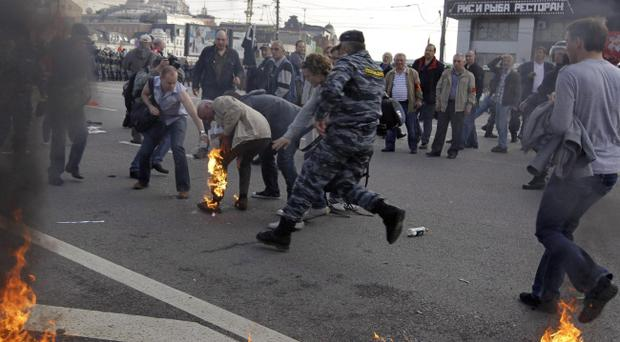 Protesters help to extinguish the clothing of a fellow protester after he caught fire from a Molotov cocktail in downtown Moscow on Sunday, May 6, 2012.