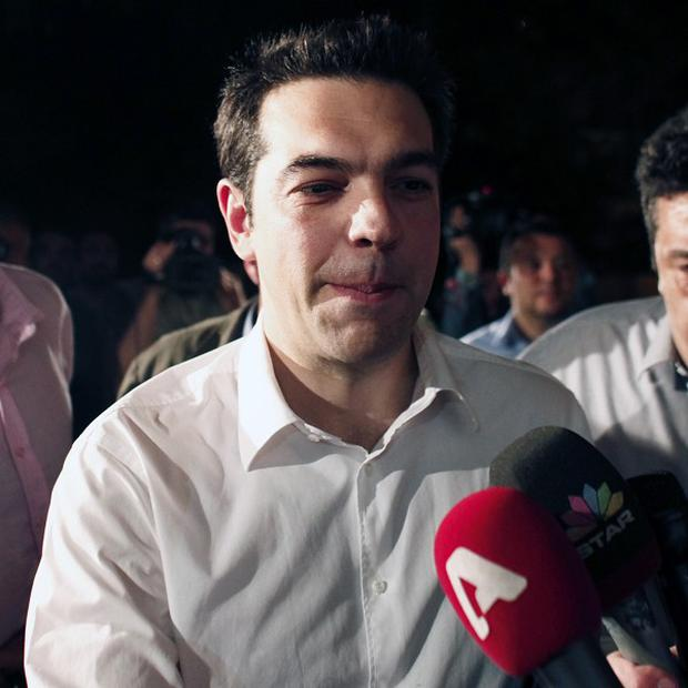 Greek leader of the Coalition of the Radical Left Alexis Tsipras arrives at the headquarters of his party in Athens (AP)