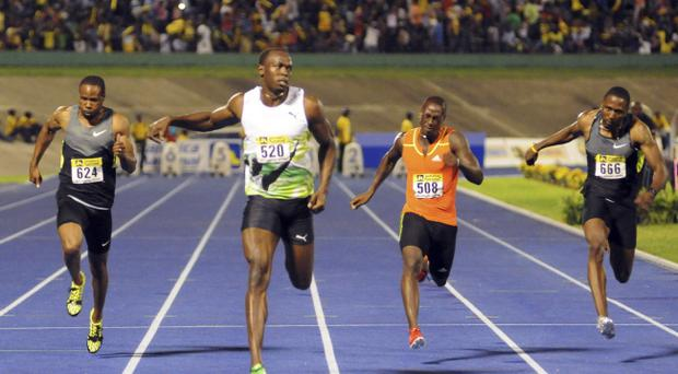 World Record holder Usain Bolt, center left, of Jamaica, crosses the finish line ahead of Antigua and Baruba's Daniel Bailey, center right, Trinidad and Tobago's Richard Thompson, right, and USA's Darvis Patton to win the 100m dash of the Jamaica International Invitational track and field meet at the National Stadium in Kingston, Jamaica, Saturday May 5, 2012. Bolt clocked 9.82 seconds to win his first 100 meters of the year. (AP Photo/Jamaica Observer Limited, Bryan Cummings) JAMAICA OUT - EDITORIAL USE ONLY