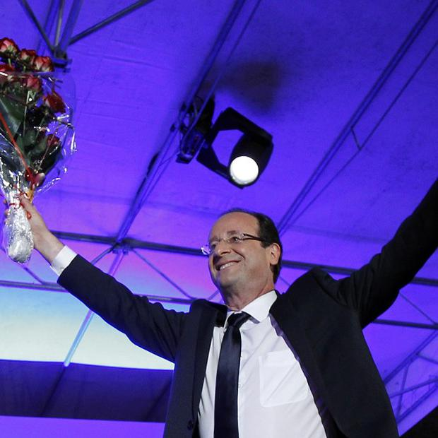 President-elect Francois Hollande holds a bouquet of roses after delivering his victory speech in Tulle, central France (AP)